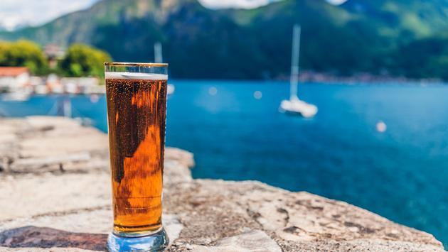 Glass of beer on the seaside stone dock. Summer refreshment (Photo via joci03 / iStock / Getty Images Plus)