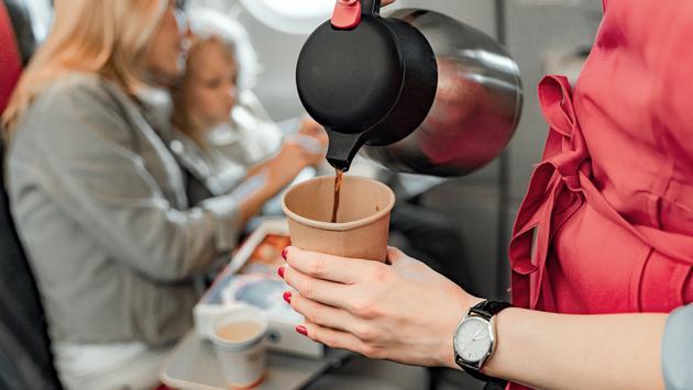 Flight attendant serving coffee mid-flight