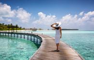 Woman walking along a wooden jetty in the Maldives.