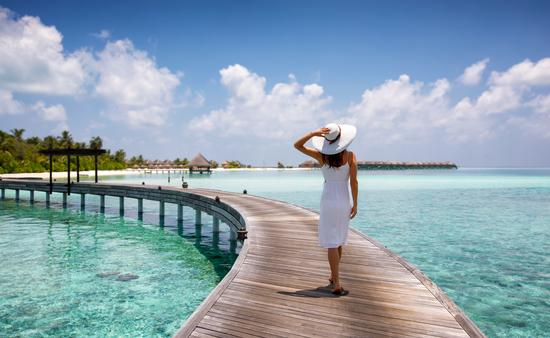 Woman walking along a wooden jetty in the Maldives.