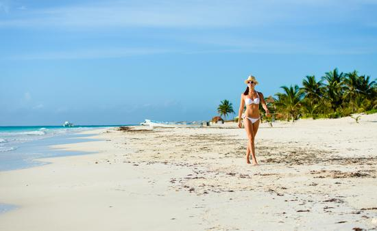 A woman walks on the beach in Riviera Maya, Mexico