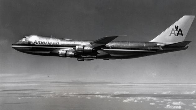 Silver four engined widebody aircraft with hump in flight
