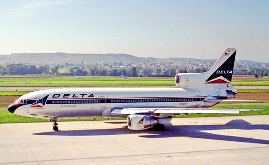 A three-engined jetliner with belonging to Delta Air Lines taken from the side on a sunny day