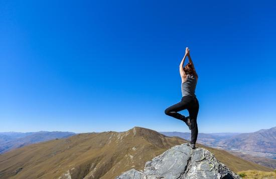 Woman practices yoga on a mountaintop in Ben Lomond, New Zealand