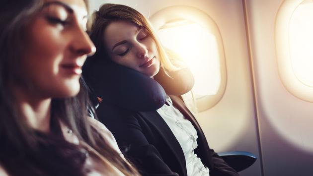 PHOTO: A female passenger sleeping on neck cushion in airplane. (photo via undrey / iStock / Getty Images Plus)
