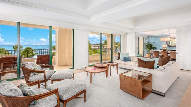 Hotel suite with white and grey furnishings and expansive ocean view
