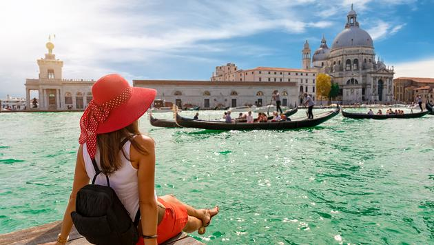 PHOTO: Female tourist looking the Basilica di Santa Maria della Salute and Canale Grande in Venice, Italy (Photo via SHansche / iStock / Getty Images Plus)