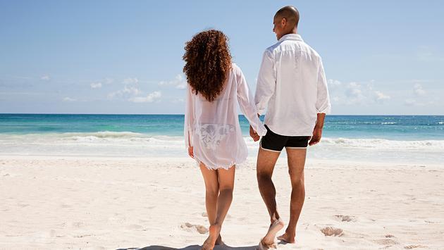 PHOTO: Couple walking on sandy beach (photo via Image Source / DigitalVision)