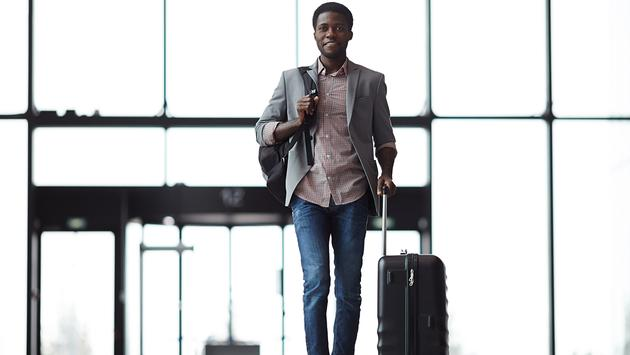 PHOTO: Man with backpack and suitcase walking along airport (photo via shironosov / iStock / Getty Images Plus)