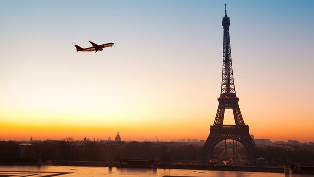 PHOTO: Eiffel tower at sunrise and airplane in the blue sky (photo via anyaberkut / iStock / Getty Images Plus)