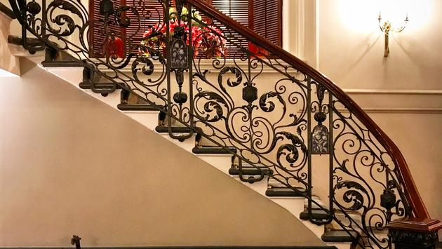 Curved staircase with flowers in lobby of Baileys Hotel London