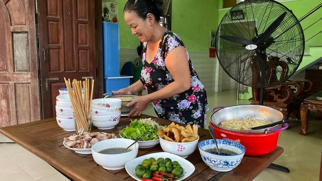 A local woman makes a bowl of cao lau.