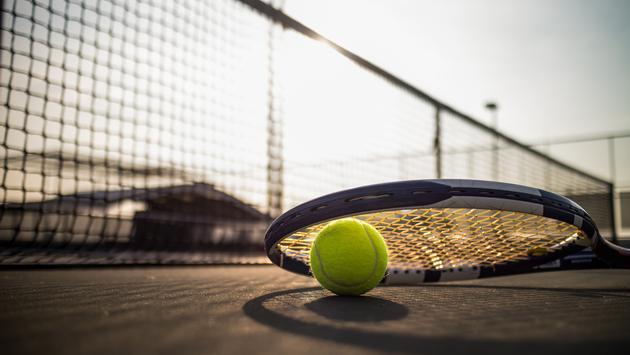Tennis ball and racquet on a hard court