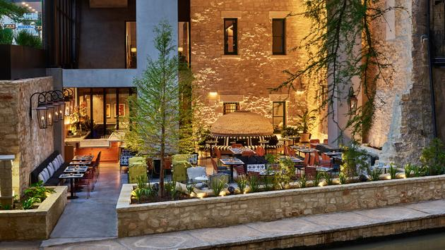 Outdoor dining on riverwalk with lighting and trees