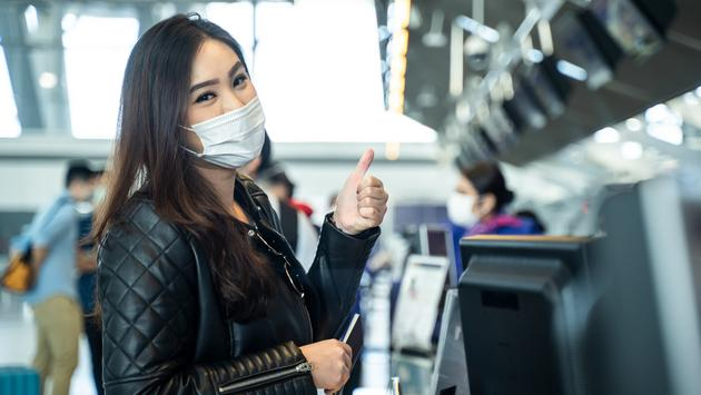 Young woman wearing a mask at airport check-in.