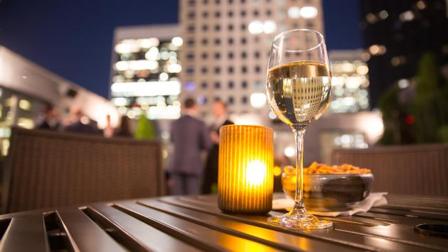 A glass of wine at a rooftop bar