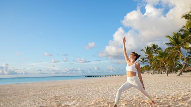 Woman doing yoga on the beach at Hyatt Zilara Cap Cana