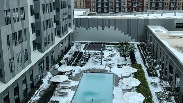Hotel courtyard covered in snow with frozen swimming pool