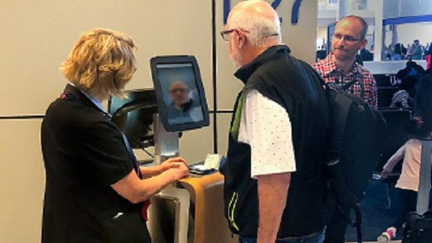 Customer boards flight at DFW using the airport's new biometric boarding technology.