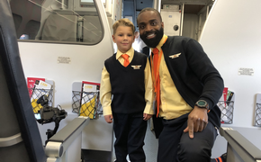 "Stephen ""SJ"" Awwad, an honorary Allegiant flight attendant for a day, shows off his crew uniform with his fellow crew member"