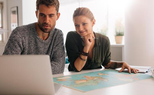 Young couple exploring the world on laptop