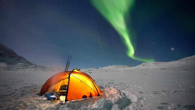 A tent set up to view the Northern Lights over Swedish Lapland