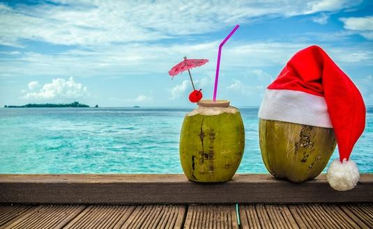 Christmas hat on coconut and coconut cocktail. (Photo via tora1983 / iStock / Getty Images Plus)