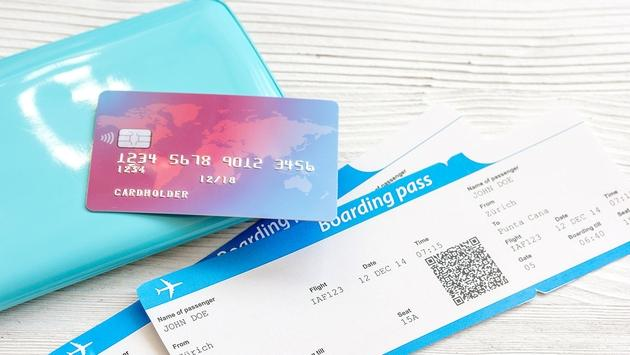 passport, credit card, tickets on wooden background (Photo via 279photo / iStock / Getty Images Plus)