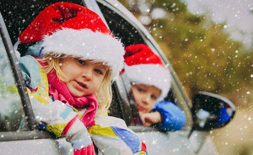 christmas car travel- happy kids travel in winter (Photo via Nadezhda1906 / iStock / Getty Images Plus)