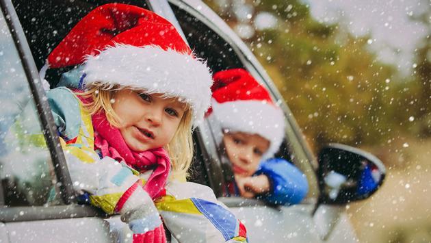 christmas car travel- happy kids travel in winter (Photo via Nadezhda1906 / iStock / Getty Images Plus)
