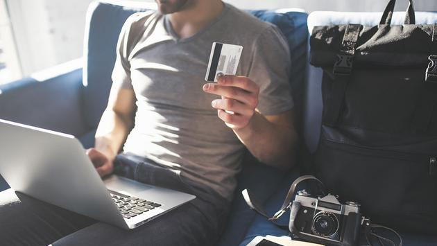 Man with laptop and credit card in hands. Preparing for traveling (Photo via Vasyl Dolmatov / iStock / Getty Images Plus)