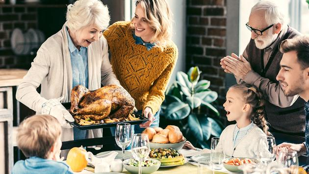 grandmother carrying turkey for family (Photo via LightFieldStudios / iStock / Getty Images Plus)