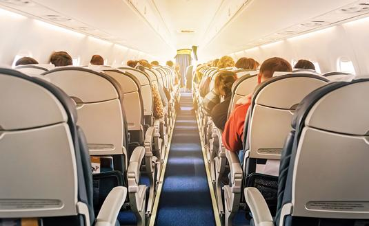 Commercial aircraft cabin with rows of seats down the aisle (Photo via Diy13 / iStock / Getty Images Plus)