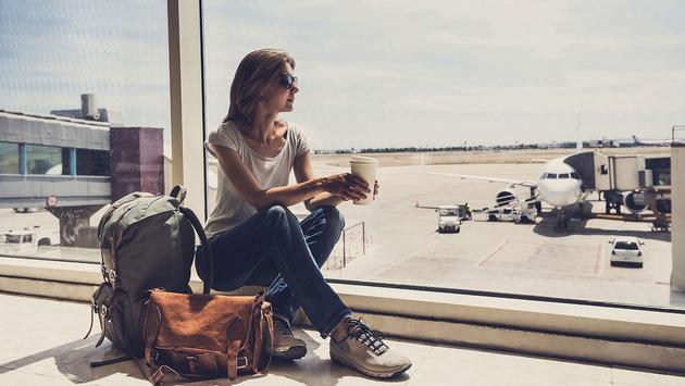 Young woman waiting for a plane. Travel concept (Photo via Poike / iStock / Getty Images Plus)