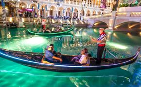 Gondoliers at The Venetian Resort Hotel & Casino pass by the Grand Canal Shops at The Venetian.
