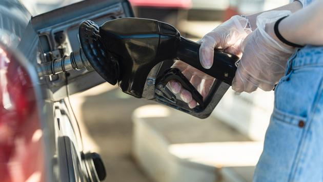 Wearing protective gloves while filling the gas tank.