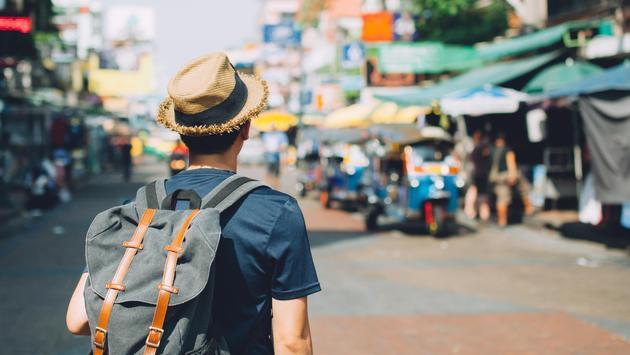 Man walking through an outdoor market in Bangkok, Thailand