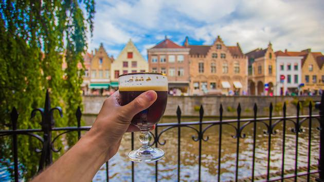 Hand holding a glass of beer in Bruges, Belgium