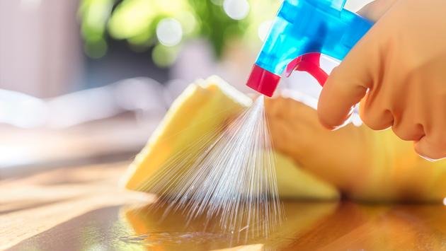 A person disinfecting a surface in their home