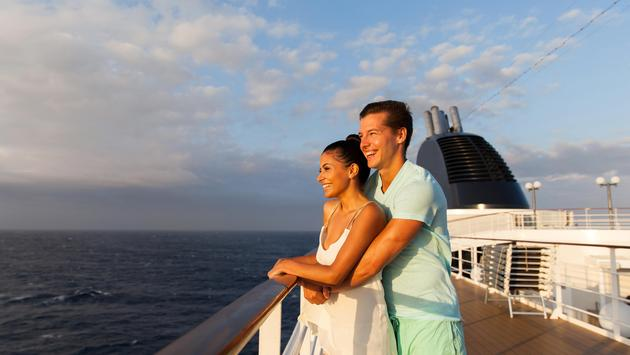 young couple looking at sunrise on cruise ship