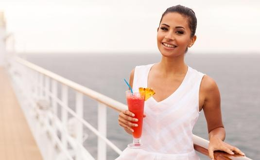 Girl holding tropical juice on cruise ship
