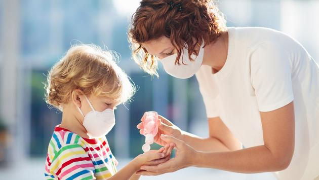 Mother and child using hand-sanitizer, masks