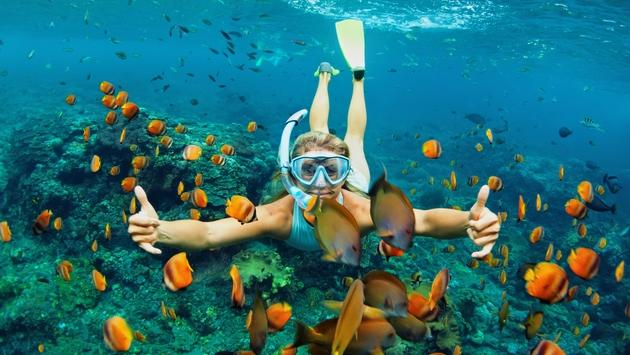 Young woman snorkeling with coral reef fishes