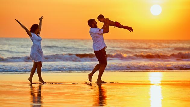 Happy family walking with fun on sunset sea beach