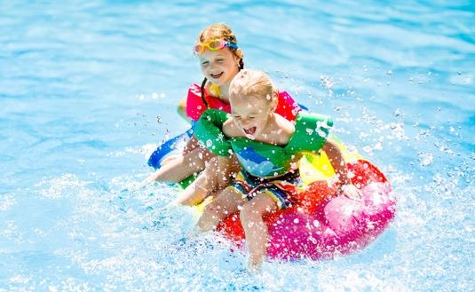 Kids on inflatable float in swimming pool