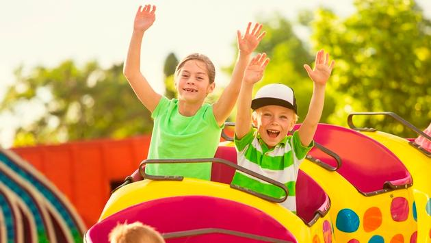 Boy and Girl on roller coaster ride at amusement park