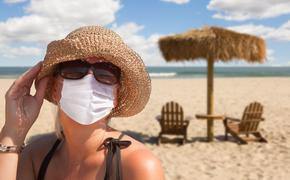 Woman vacationing on a sandy beach wearing a mask.