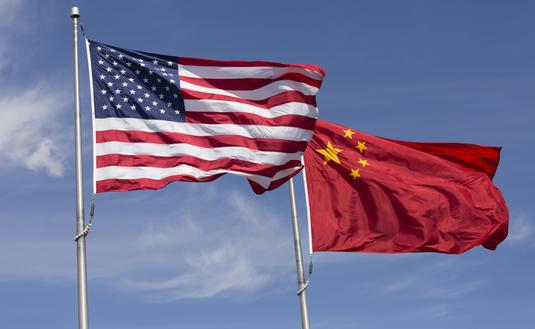 American Chinese windy day flags fly together on flagpole