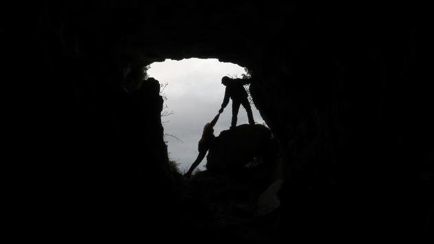 Man rescuing another from a cave