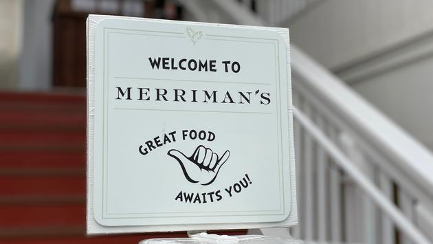 """Sign reading """"Welcome to Merriman's - Good Food Awaits You"""" with a shaka hand gesture"""